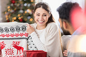 A young woman both smiles and grimaces as she holds up a Christmas sweater she has just opened for her unrecognizable friend to see.  She is sitting on the couch in her living room.