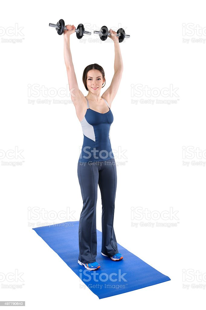 young woman shows finishing position of shoulder press stock photo