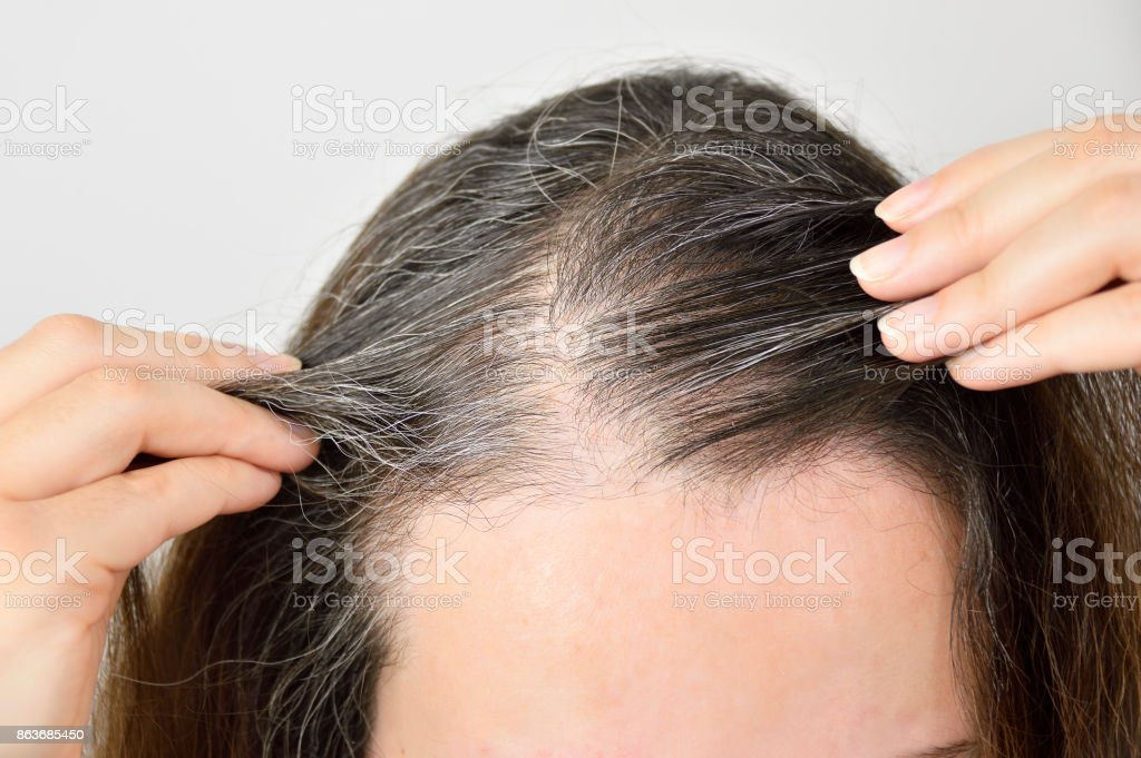 Young woman shows her gray hair stock photo