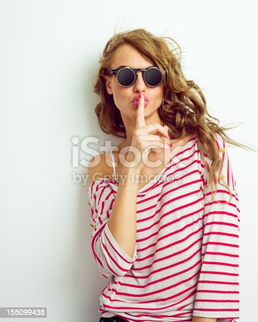 Portrait of pretty young woman wearing striped top and sunglasses, holding finger on her lips, Studio shot, white background.