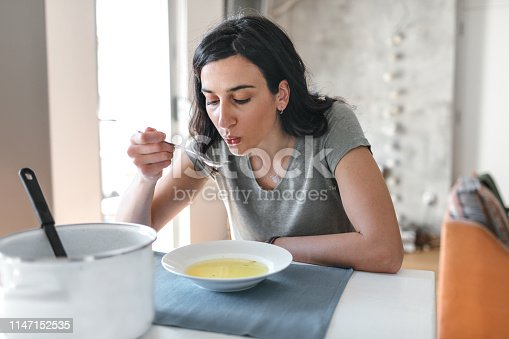 Young woman sick at home eating soup.