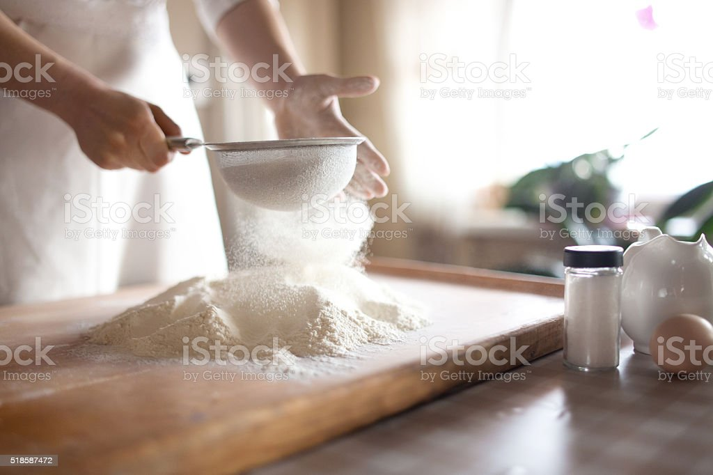 young woman sifting flour into bowl at the kitchen​​​ foto