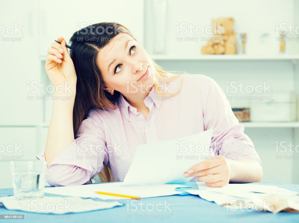 Young woman  signing agreement papers  at home royalty-free stock photo