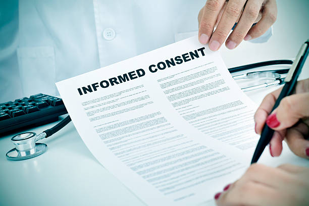 young woman signing an informed consent - permit stock photos and pictures