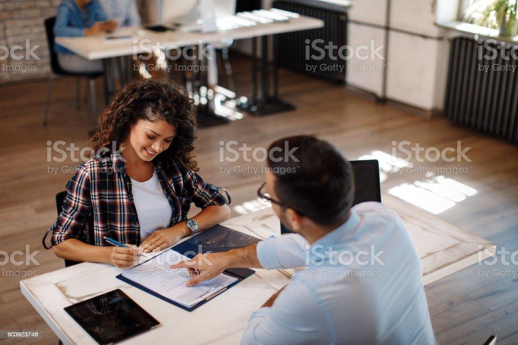 Junge Frau, die Vertragsunterzeichnung mit manager – Foto