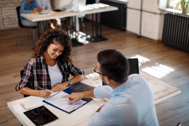 Young woman signing contract with manager stock photo