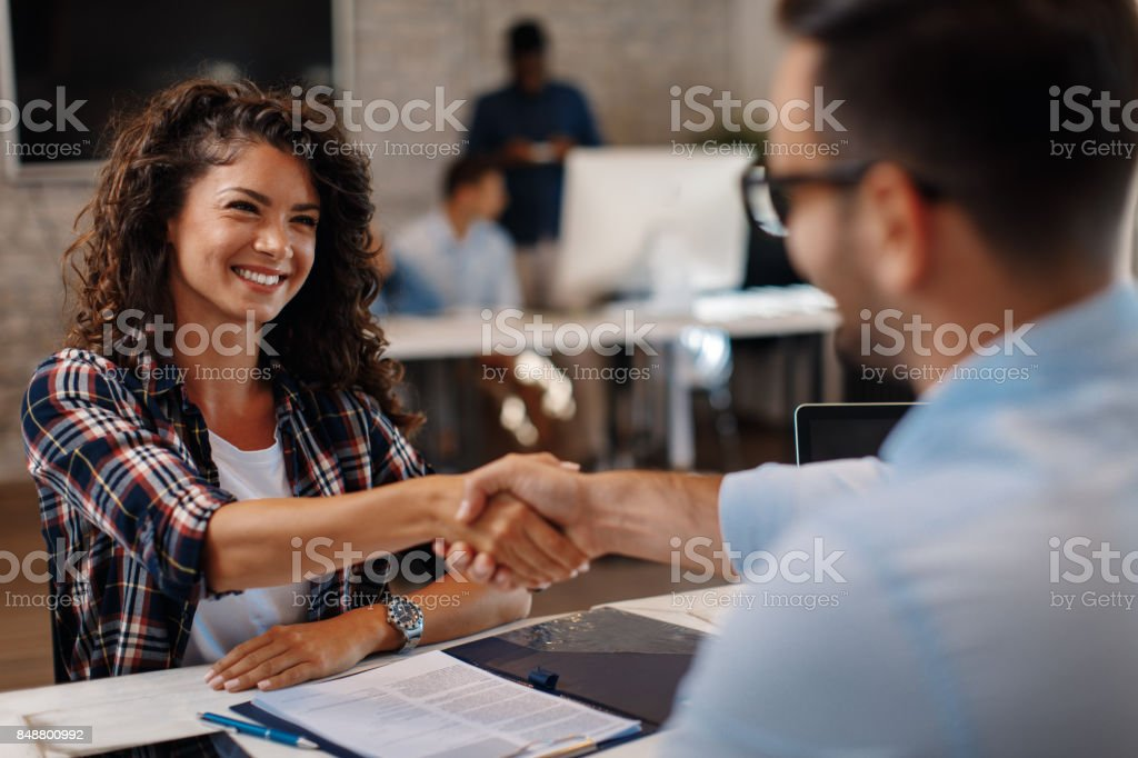 Young woman signing contracts and handshake with a manager royalty-free stock photo