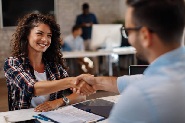 Young woman signing contracts and handshake with a manager stock photo