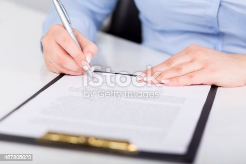 638881988istockphoto Young woman signs a contract 487805623