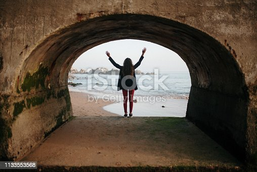 The silhouette of a young woman with arms raised inside an arch of a jetty by the sea