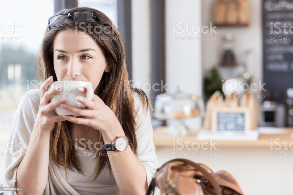 Young woman sips coffee in coffee shop stock photo