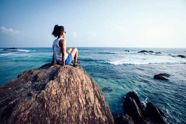 Junge Frau sitzen auf Dem Meer Felsen Klippe Denken – Foto