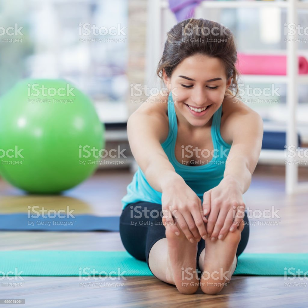 A Caucasian woman is smiling and looking down as she sits on her...