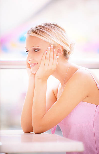 Young woman sits at little table  restaurant stock photo