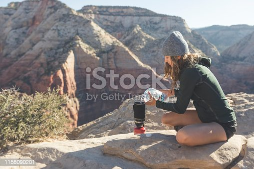 A young woman sits by herself at the edge of a steep cliff in the Utah desert and makes herself a cup of coffee in a portable stove that she's pouring water into. Ahead is a range of mountains.