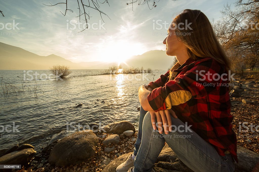 Young woman sits by the lake, watches the sunrise stock photo