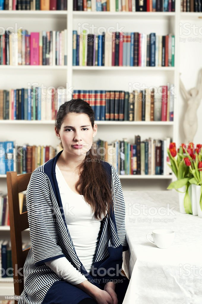Young woman sits in front of large bookshelf royalty-free stock photo