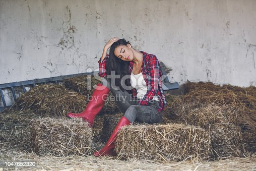 a young woman sits in the hay in the stable and looks in the direction of the camera