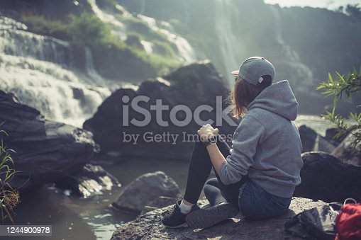 Young woman sits on a rock at the waterfall. Rear view.