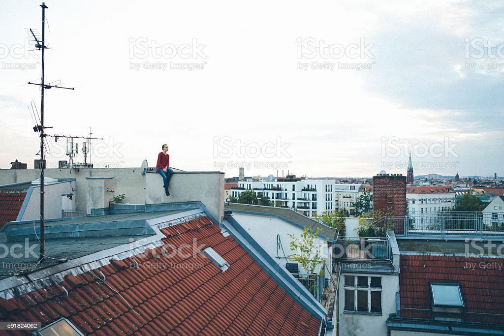 young woman sits on a roof and look far away – Foto