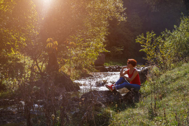 Young woman sits on a stone near a small stream on a sunny autumn day stock photo