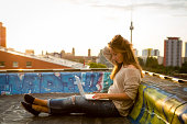 istock young woman sits on roof, works on laptop - back lit 508401059