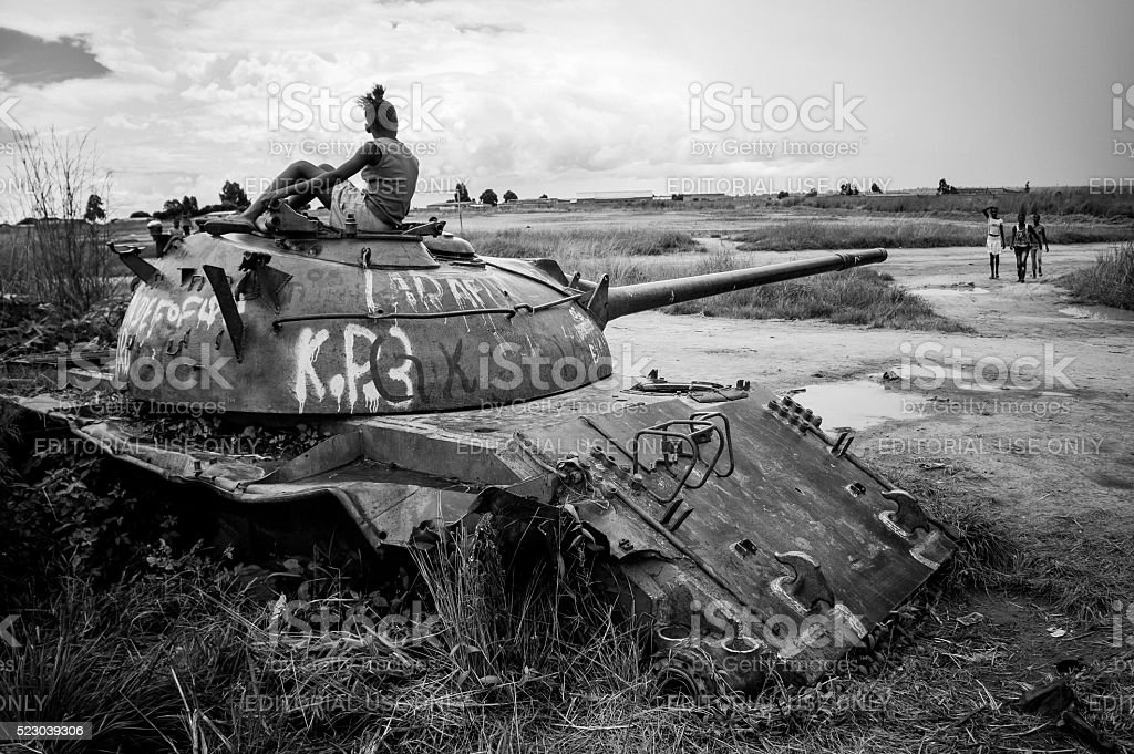 Young woman sits on top of an abandoned tank. stock photo