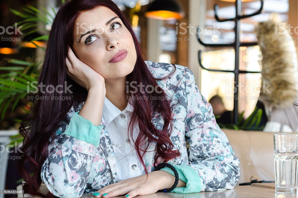 Young woman sitting alone in a cafe or restaurant - foto de acervo