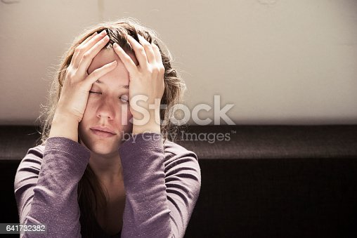 istock Young woman sitting alone looking sad 641732382