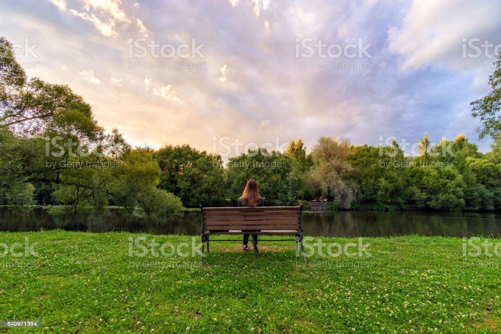 Une jeune femme assise seule sur un banc dans le parc vert - Photo