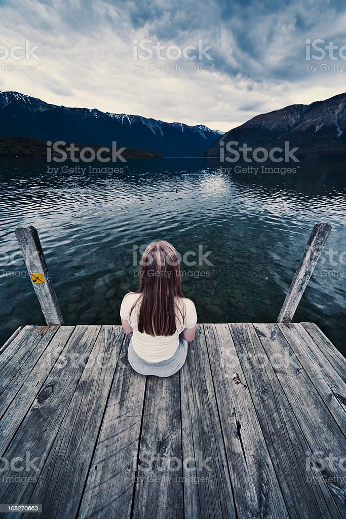 Young Woman Sitting alone on dock royalty-free stock photo
