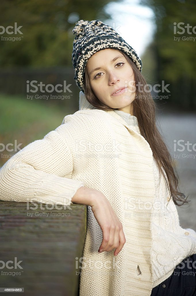 Young woman sitting alone outdoors with sweater and hat royalty-free stock photo