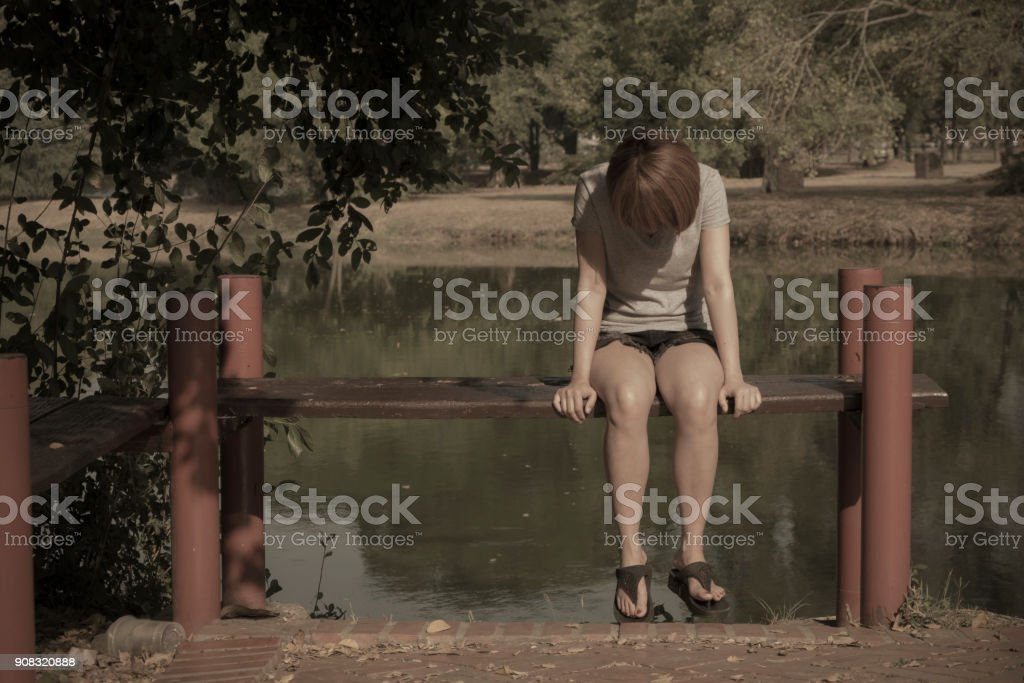 Young woman sitting alone stock photo