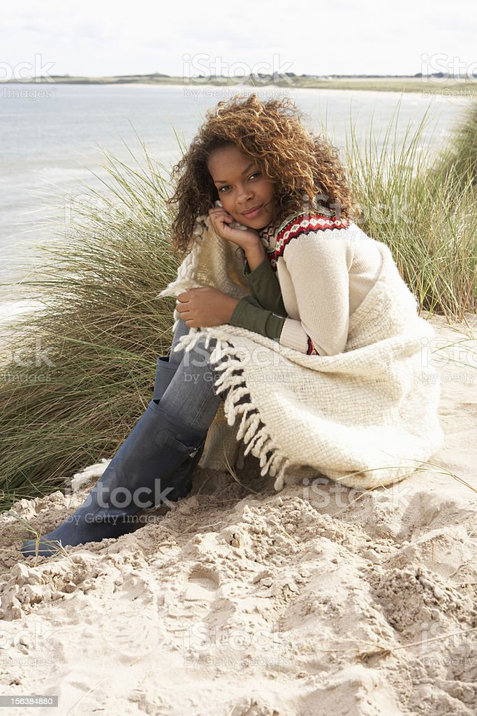Young Woman Sitting Amoungst Sand Dunes Wrapped In Blanket stock photo