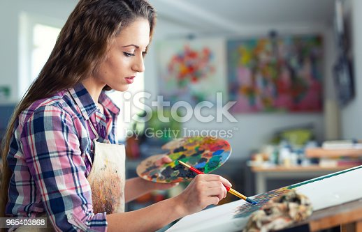 istock Young woman sitting and drawing 965403868