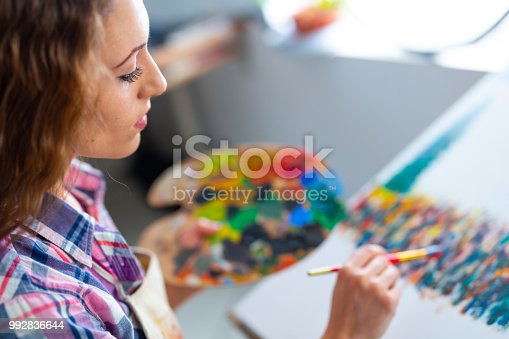 istock Young woman sitting and drawing 992836644