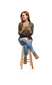 A portrait of a young woman sitting on a wooden stool and holding a tablet while looking over at a copy space.