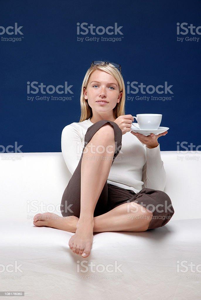 Молодая женщина сидит и держит Чайная чашка стоковое фото