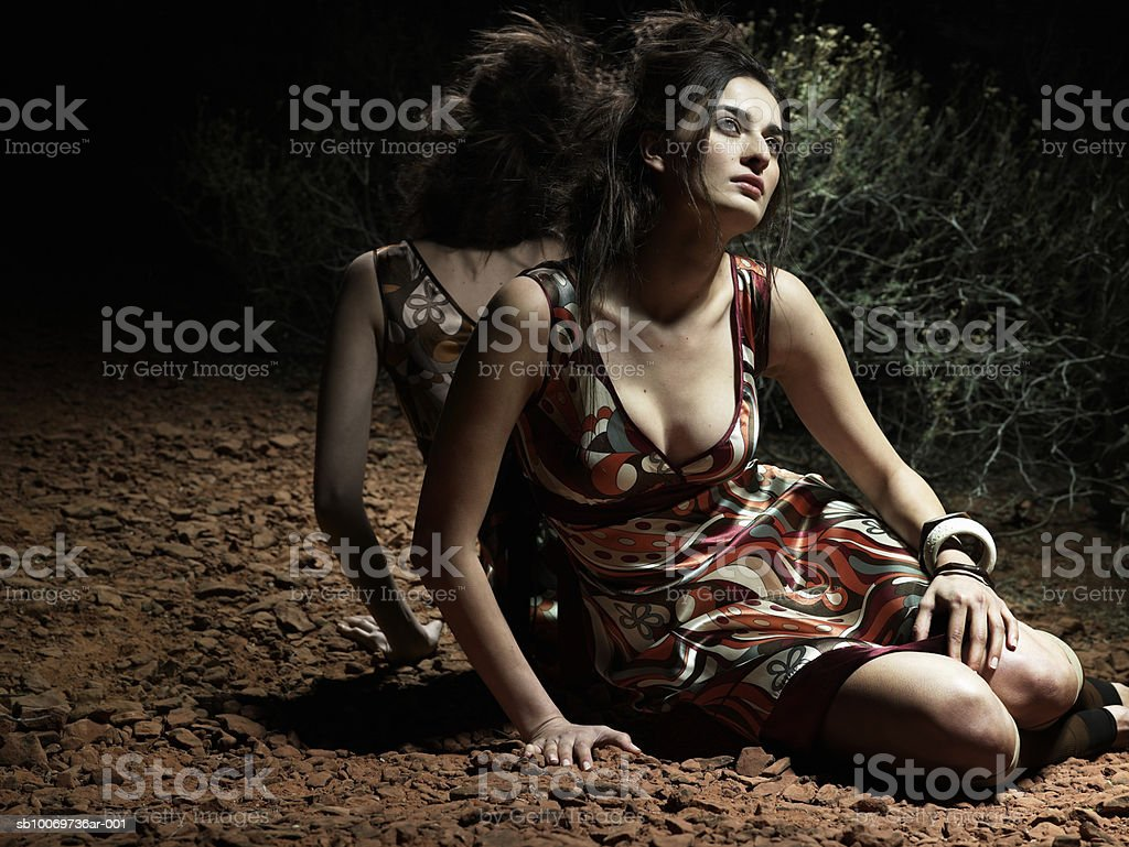 Junge Frau sitzt und Wegsehen Lizenzfreies stock-foto