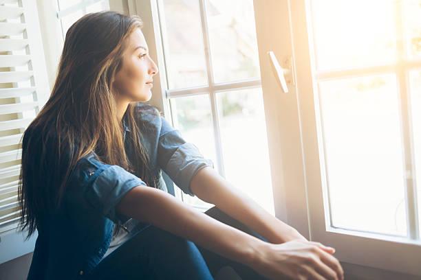 Junge Frau sitzt und Blick durchs Fenster – Foto