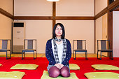 Young woman sitting and meditating in Japanese tatami roon in temple