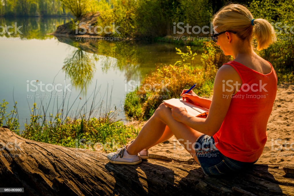 young woman sitting at a lake and writing in her diary stock photo