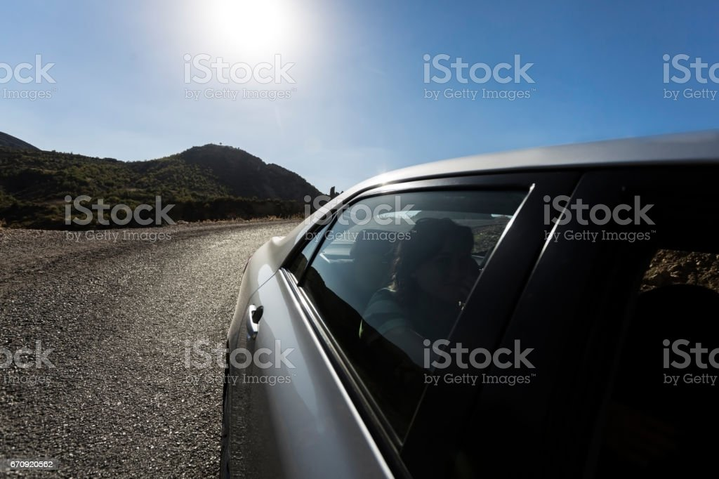Young woman sitting at back seat in car - Foto stock royalty-free di Abbigliamento casual