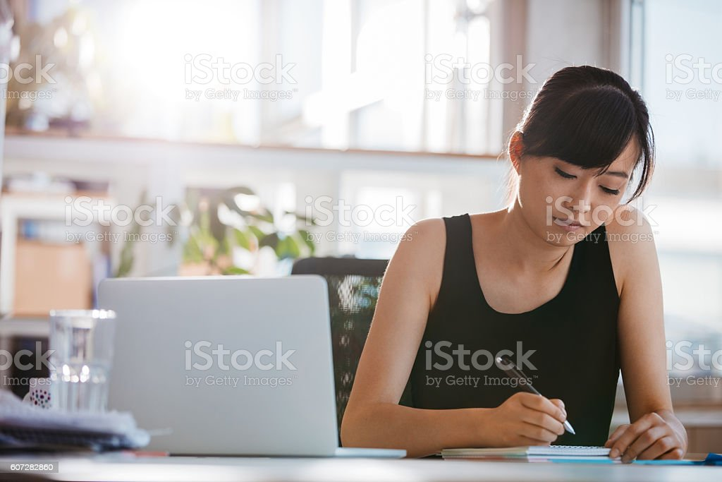Young woman sitting at desk and writing notes stock photo