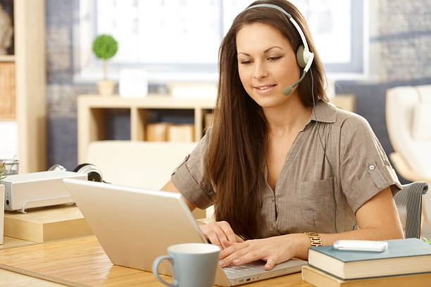 Young woman sitting at her desk with her headset and laptop stock photo
