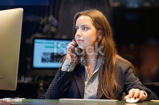 1167562098 istock photo Young woman sitting at her desk working and answering a phone call. 1188225638