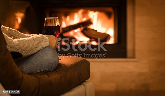 istock Young woman sitting at home by the fireplace and drinking a red wine. 846414408