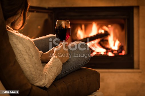 istock Young woman sitting at home by the fireplace and drinking a red wine. 846414424