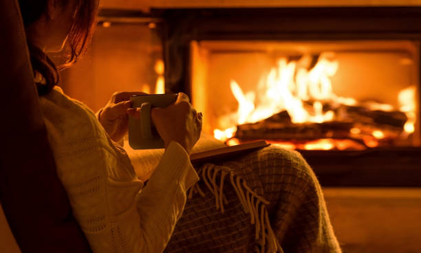 Young woman sitting at home by the fireplace and reading a book. Young woman sitting at home by the fireplace and reading a book. evaporation stock pictures, royalty-free photos & images