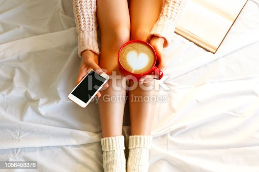 istock Young woman sitting at home. Close up of female legs clean shaven with smooth skin. 1056453376